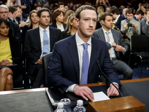 zuckerberg sits at a table in front of a microphone with a large audience seated behind him