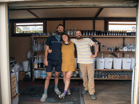 two bearded men in their 30s and one woman in her 30s stand smiling in a garage with rows of glass bottles on shelves behind them