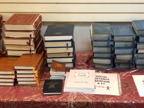 "signs that say ""stay six feet apart"" sit out on a table with stacks of prayerbooks"