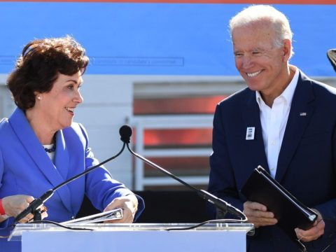 a middle-aged woman at a podium, next to Biden