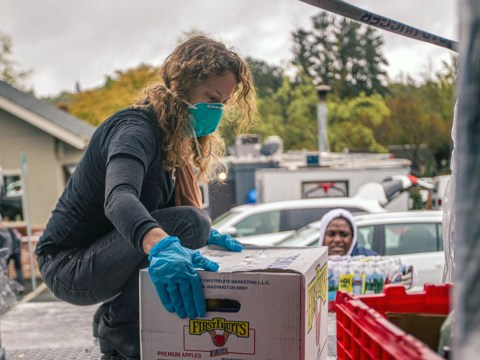 A woman kneels in the back of a large delivery truck to pick up a box of produce