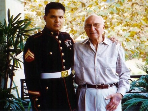 a young latino man in a marines dress uniform poses with an elderly man
