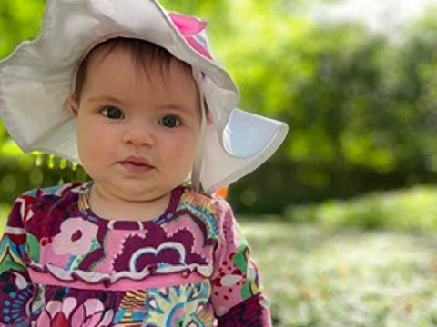 a baby seated in a colorful floral dress and white hat outside