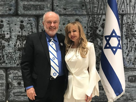a middle aged white man in a suit and Israeli flag tie stands with a middle aged woman in a white pantsuit