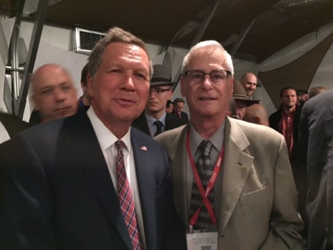 an older white man in glasses stands with Gov. John Kasich in a crowded room