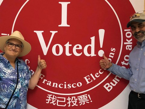 """a middle aged man and woman pose with their thumbs up in front of a large """"I Voted"""" sign"""