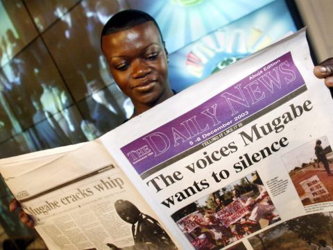 Moyo is seen in 2003 holding a special edition of the newspaper where she worked, which was banned by Zimbabwe's government. (Photo/JTA-PA Images via Getty Images)