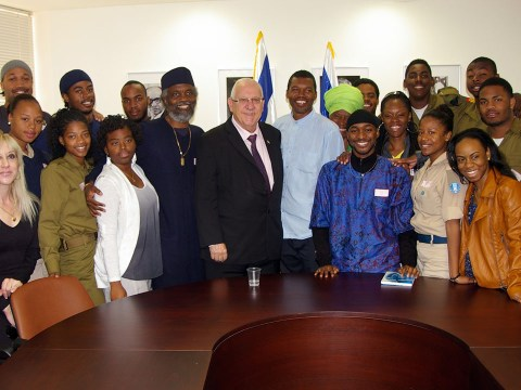 Around 20 Black adults of varying age, some in Israeli military uniforms, pose for a group picture with Israeli President Reuven Rivlin, an older white man.