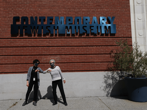 CJM's COO and interim executive director Kerry King and board chair Joyce Linker stand outside the CJM's front entrance on opening day. (Photo/Forward-Sarah Brown)