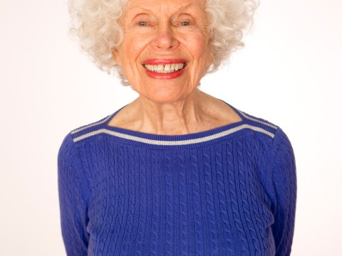 woman with blue sweater and curly white hair smiling