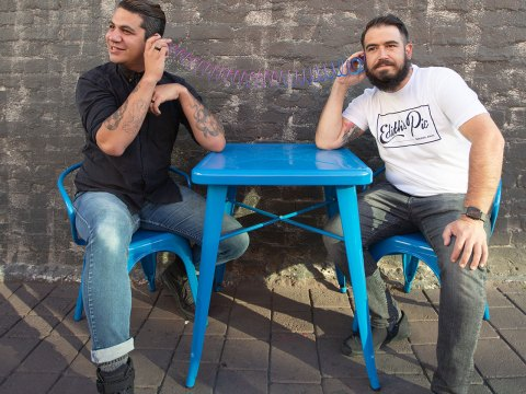 two 30-something-looking white guys sitting at a blue table