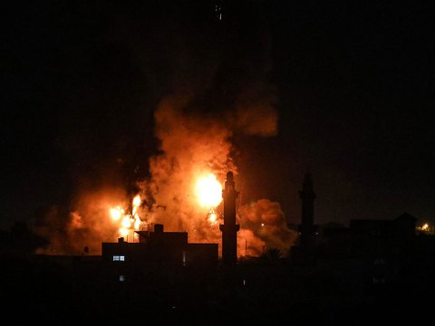 flames illuminate thin mosque towers against a night sky