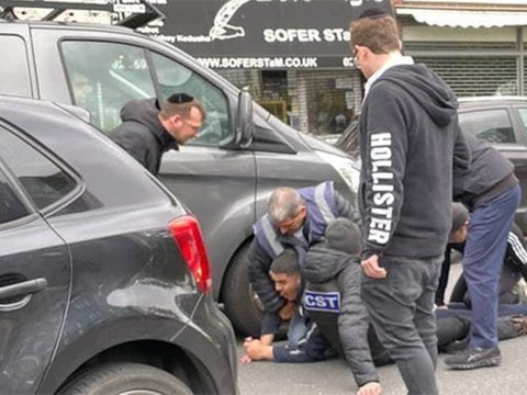 Men from the CST and Shomrim security units detain a man whom witnesses said assaulted a Jewish man in a car in London, May 21, 2021. (Photo/JTA-Eye on Antisemitism)
