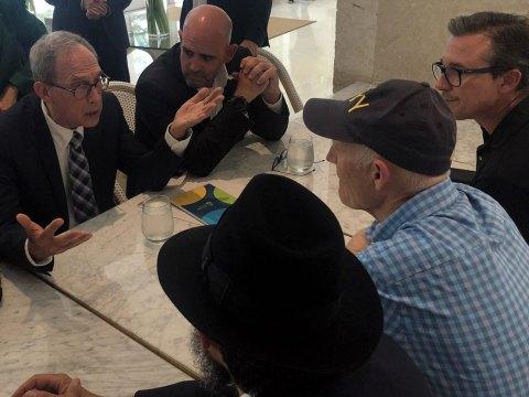 Nachman Shai (left) speaks to Sen. Rick Scott (second from right) at the Grand Beach Hotel in Surfside, Florida, June 27, 2021. (Photo/JTA-Ron Kampeas)