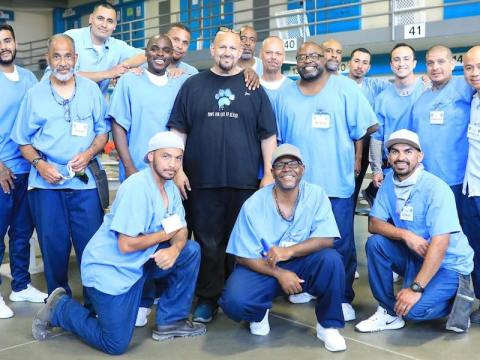 Jon Grobman (center) poses with a group of incarcerated men at California State Prison, Los Angeles County, in Lancaster. His own prison term behind him, Grobman now works as director of programs for Paws for Life K9 Rescue, which has incarcerated men train shelter dogs. (Photo/JTA-Courtesy of Rita Earl Blackwell)
