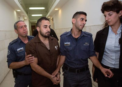 Khalil Adel Khalil (second from left), 25, of the A-Tur neighborhood in Jerusalem, is brought to Jerusalem's District Court on July 9, 2015. Khalil, who admitted to trying to join the Islamic State terror group in Syria, was sentenced to two years in prison. Credit: Yonatan Sindel/Flash90.