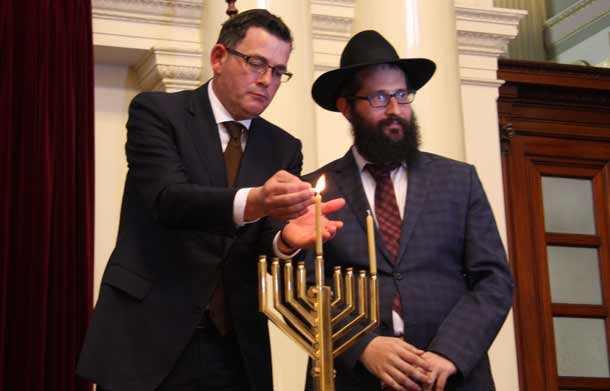 Premier Daniel Andres lights the Shammos watched by Rabbi Chaim Herzog