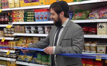 Rabbi Feldman cuts the ribbon