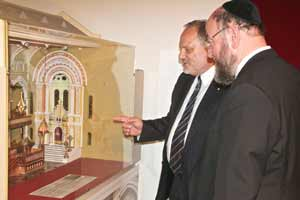 Stephen Rothman shows Chief Rabbi Ephraim Mirvis a model of the building