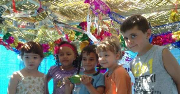Maria (age 5) of Ukraine, Gavriel (age 5) of Yemen, Annamalai (age 5) of Peru, AJ (age 6) of South Africa, and Sofia (age 4) of Argentina—all of them recent immigrants to Israel—pose in the sukkah they helped build at The Jewish Agency's Ye'elim Immigrant Absorption Center in Be'er Sheva, Israel Photo by Tali Nehama, The Jewish Agency for Israel.