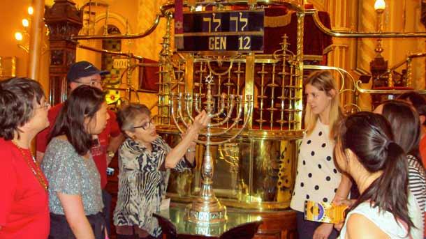 Volunteer tour guide Susan Bures shows visitors the silver Rabbi Falk Chanukiah.