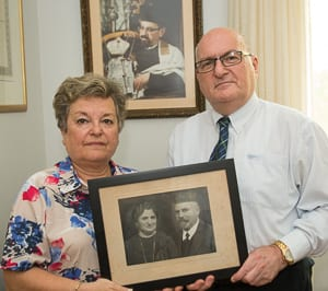 Three generations: A photo of Rabbi Benjamin Gottshall hangs behind Eva Wittenberg and Alex Gottshall who hold a photo of Rabbi Samuel and Rebbetzin Eva Gottshall.     Photo: Henry Benjamin