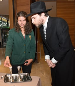 Jessica Fox light the Shabbat candles watched by Rabbi Levi Wolff