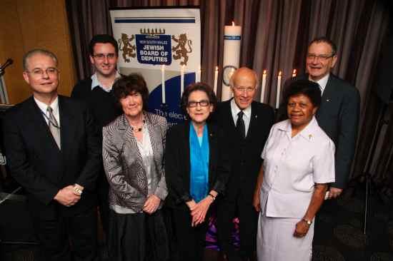The candle lighters, from left: Leo Tucker, Glen Falkenstein, Professor Bettina Cass, Marika Weinberger, Professor Ron Penny, Sister Sesarina Bau, Professor David Cooper.