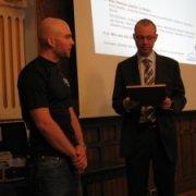 Timo Koivisto luovuttamassa tunnustuspalkintoa Teemu Tenhuselle.