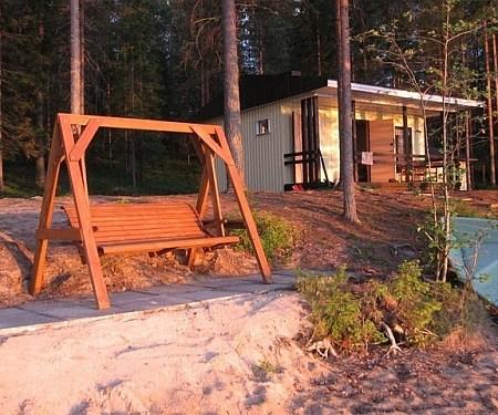 Edustalla rantapatio ja keinu, taustalla näkyy saunatupa.