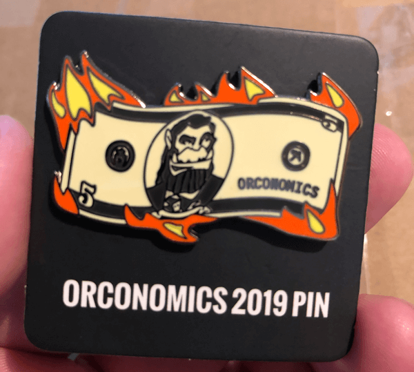 An image of a pin with an orc on a flaming bill