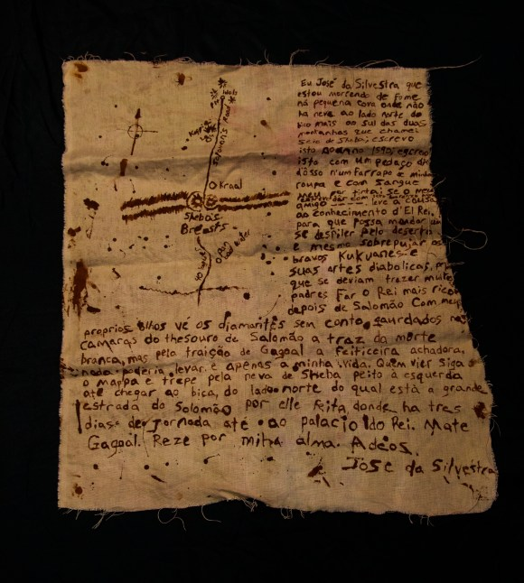 Map to Kukuanaland. A torn piece of linen covered with rust colorad writing and a rough map
