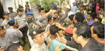 NYARIS BENTROK: Polisi menghadang massa yang akan mendekati ruang tahanan