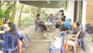 BERKABUNG: Warga berada di depan rumah duka di Desa Gendohkemarin.