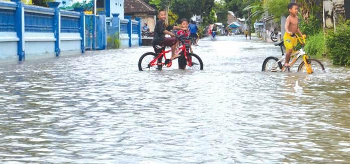 Sejumlah-anak-anak-bersepeda-di-jalan-raya-yang-tergenang-air-di-Dusun-Krajan,-Desa-Tembokrejo,-Kecamatan-Muncar,-Banyuwangi,-kemarin.