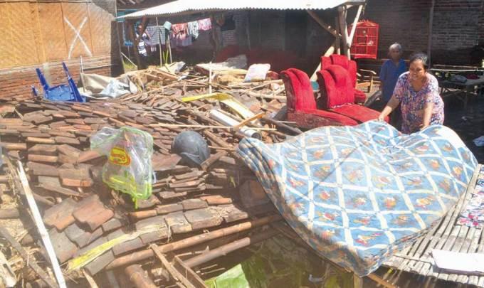 Sutini,-32,-menjemur-kasur-yang-sudah-basah-di-dapur-rumahnya-yang-ambruk-di-Kecamatan-Muncar,-Banyuwangi,-kemarin