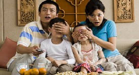 Family watching television with parents covering children's eyes