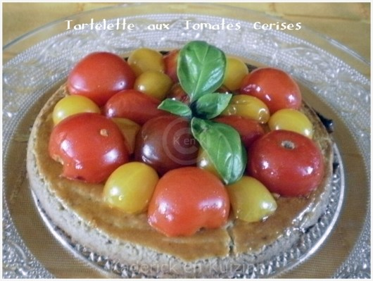Recette de mini tartelette tomates cerises bio pour une entrée servi avec une feuille de basilic
