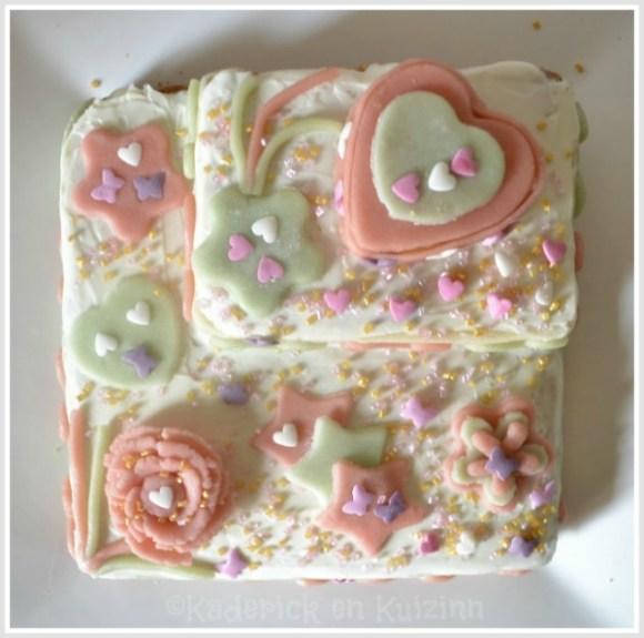 Recette du gateau fête des mères vue de dessus décoré de fleur et de coeurs en pâte d'amande verte et rose