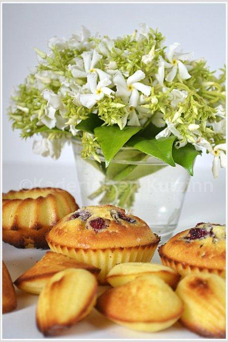 Présentation des madeleines au citron bio de différentes formes avec un petit bouquet de jasmin blanc étoilé