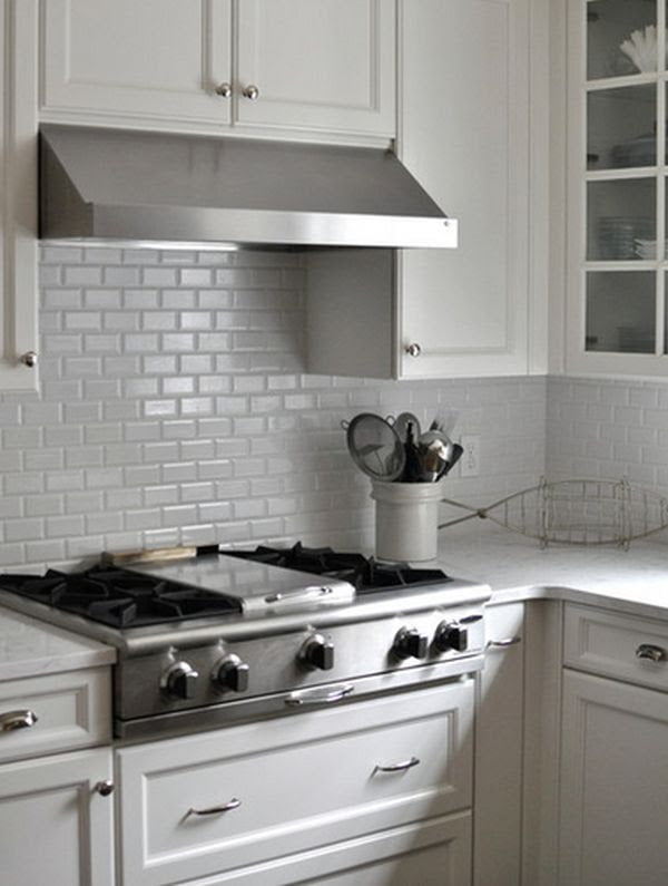 A traditional kitchen showcasing a white backsplash and matching cabinets