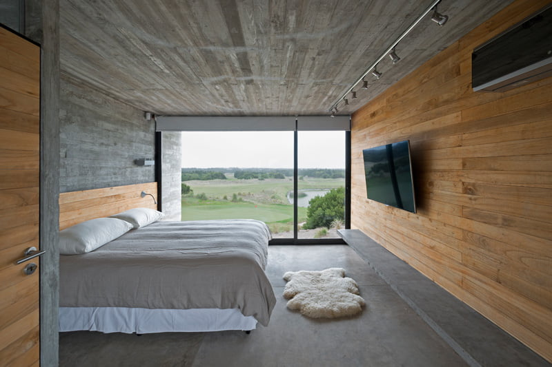 exposed concrete modern house master bed with golf view