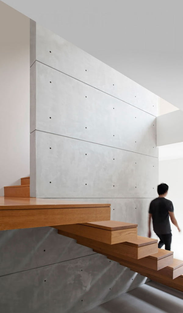Wooden finished staircase with exposed concrete wall