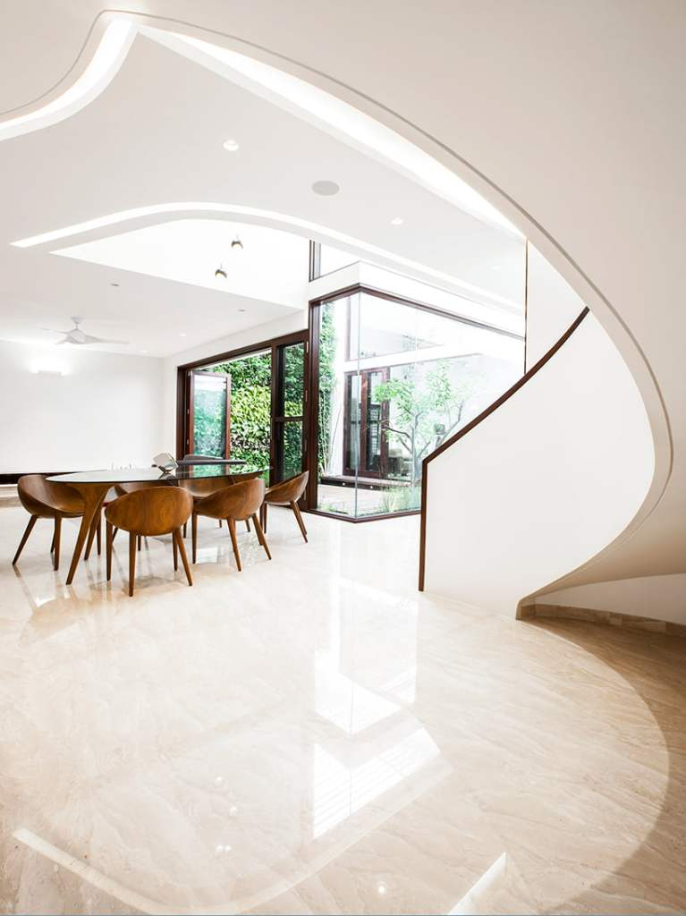 fully lighten and airy dining area with spiral white color stair with it