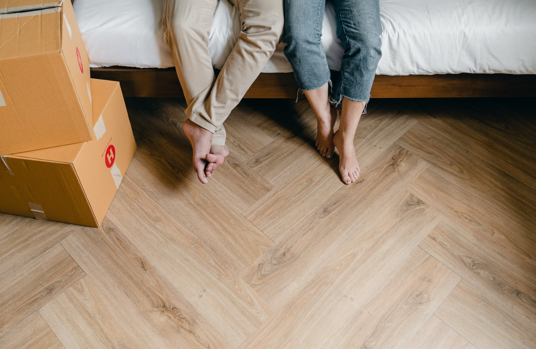 crop young couple with carton boxes in new apartment