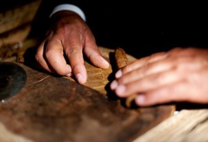Tobacco leaves being rolled into a cigar. Source: ctcigarco.com