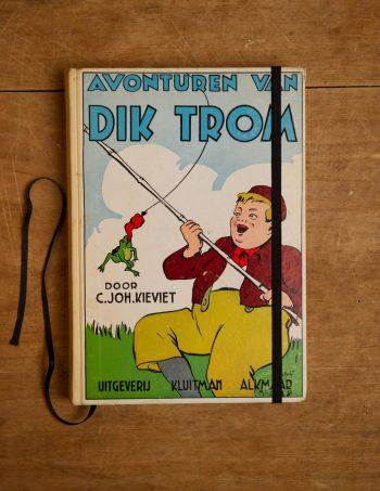 """Van het kinderboek """" Avonturen van Dik Trom _ 11e druk"""" hebben we een notitieboekje gemaakt. Blanco pagina's, voorzien van een zwart elastiek en een lintje."""