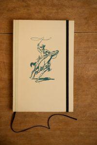 """Van het jongensboek """" Arendsoog 16 - Het Veeland in gevaar"""" is een notitieboekje gemaakt. Blanco pagina's, voorzien van een zwart elastiek en een lintje.n"""