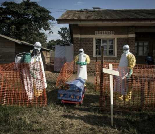 Des médecins désinfectent le cercueil d'un malade décédé, dans un centre de traitement d'Ebola, le 13 août 2018 à Beni, en République démocratique du Congo | AFP | John WESSELS