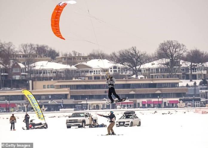Les gens qui volent en snowkites sont vus profiter de la neige samedi à Wayzata, Minnesota